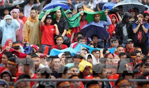Cổ động viên đội mưa cổ vũ cho đội tuyển bóng đá U23 Việt nam tại NVH Thanh Niên (Tp Hồ Chí Minh). Ảnh: Quang Nhựt – TTXVN