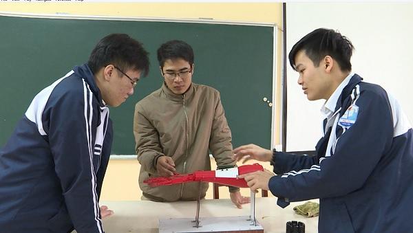 Em Bình (phải), Cường (trái) và thầy giáo Lê Đức Thiện đang giới thiệu về cơ chế hoạt động của cánh tay rô bốt